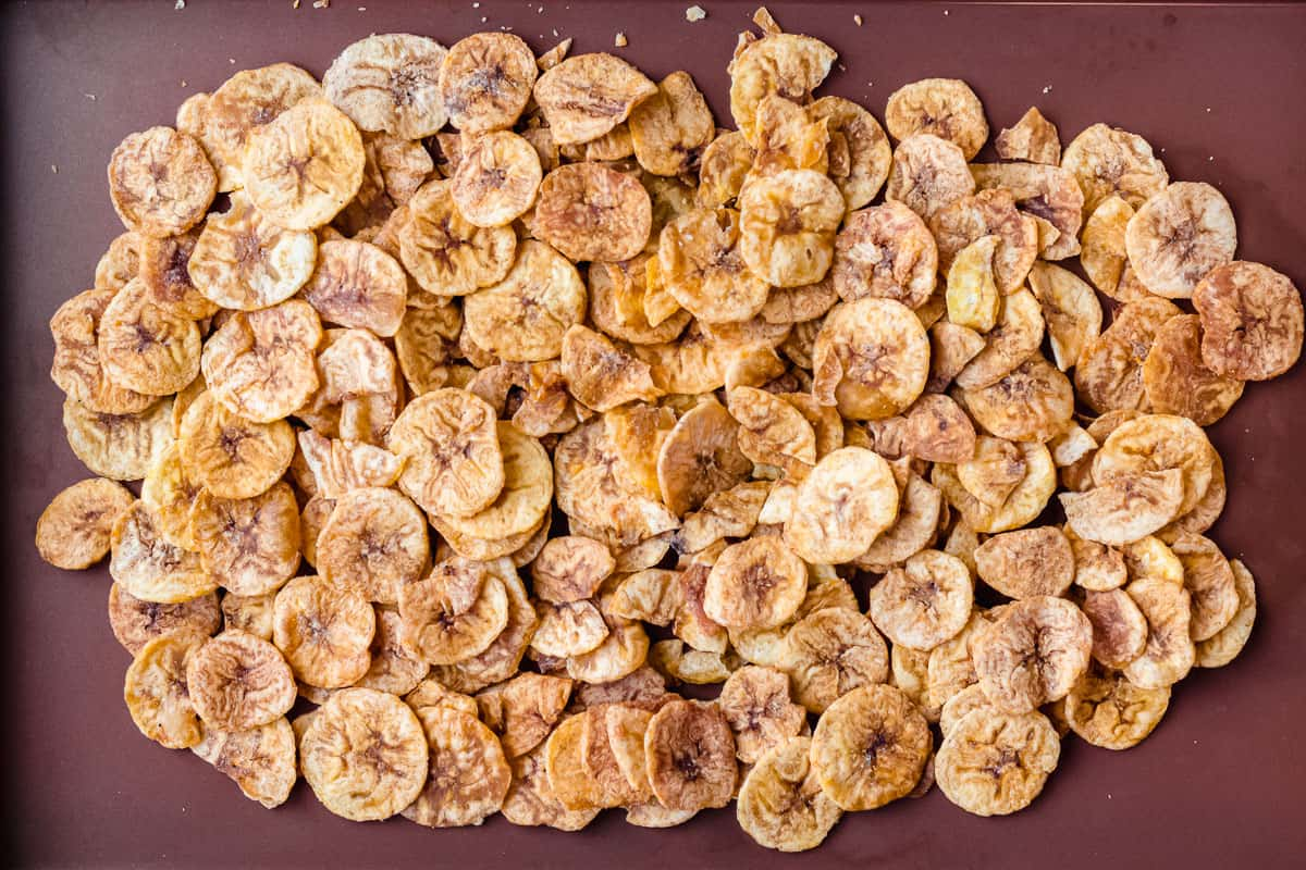 Plantain chips spread out onto a baking sheet
