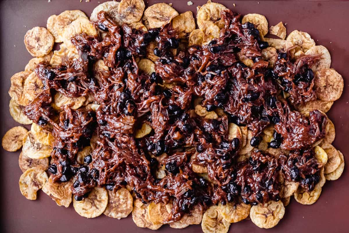 Plantain chips topped with pulled pork and black beans on a sheet pan