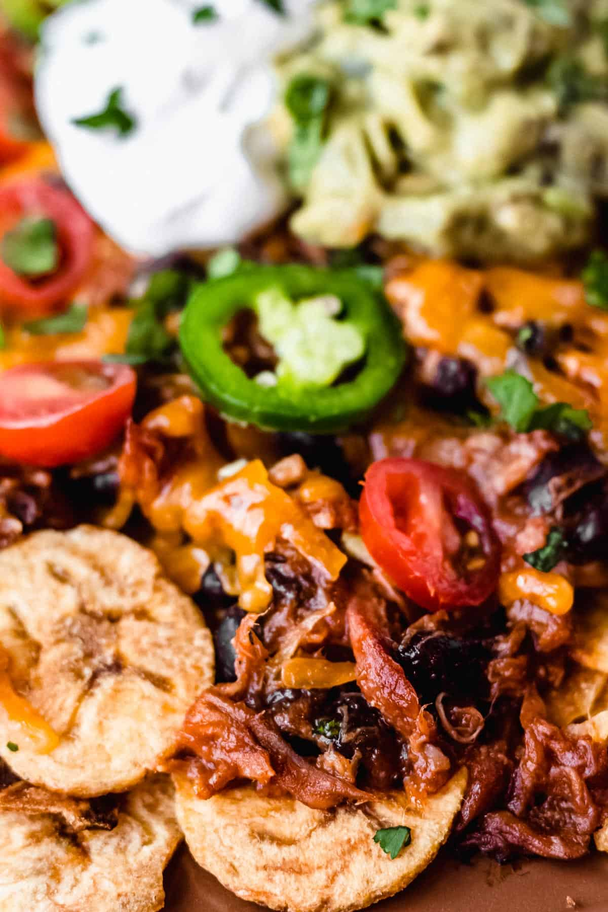 Close up of pulled pork nachos on plantain chips with sour cream and guacamole blurred in the background