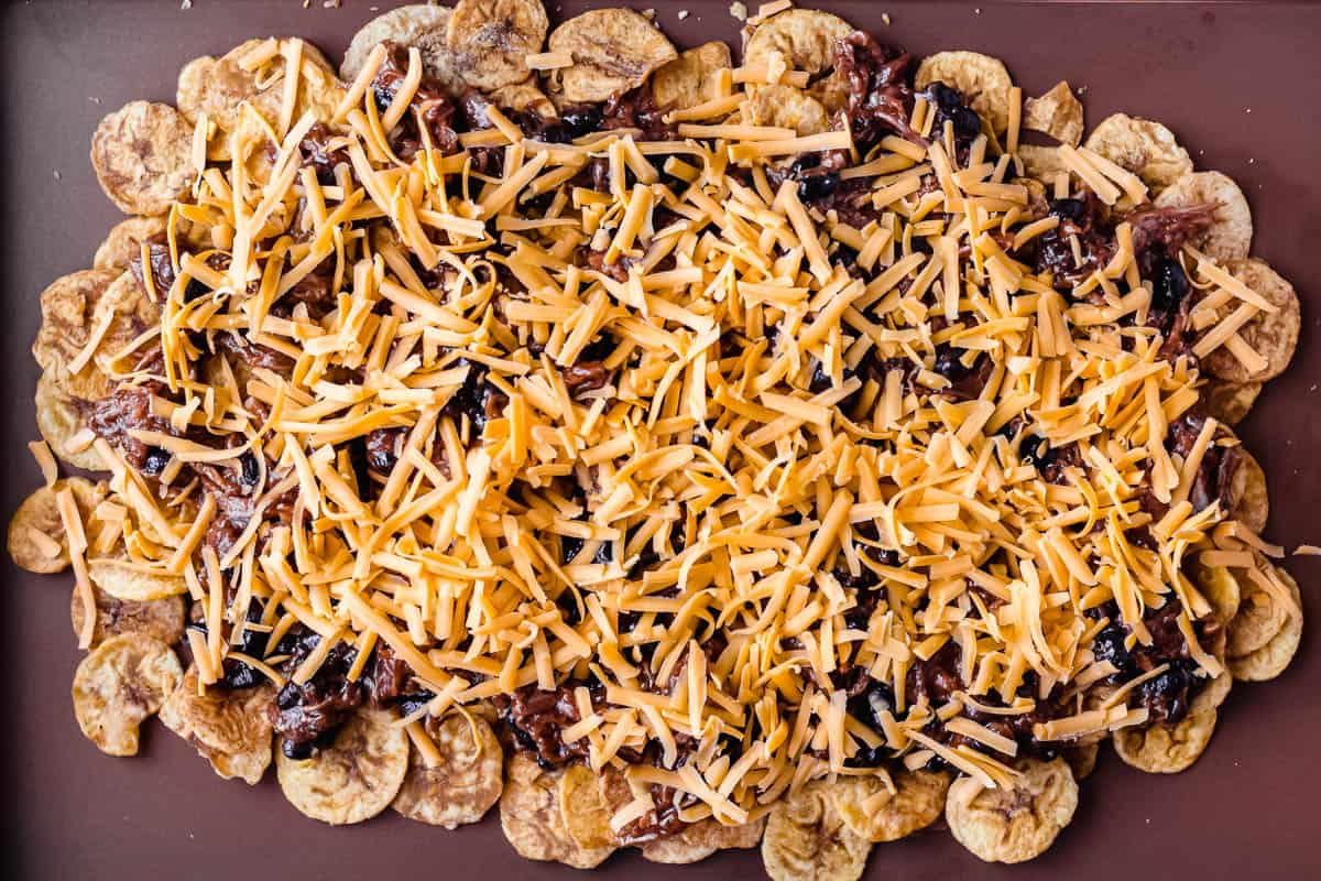 Plantain chips topped with pulled pork, black beans and shredded cheese on a sheet pan