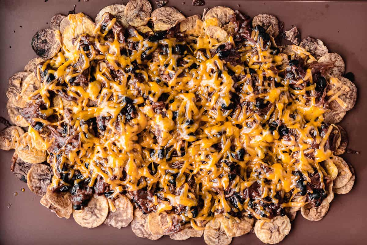 Baked pulled pork nachos on plantain chips on a sheet pan