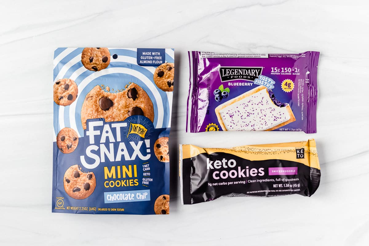 a package of fat snax cookies, keto toaster pastries and keto cookies on a white backdrop