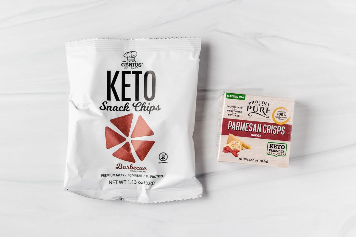 A bag of keto chips and box of parmesan crisps on a white backdrop