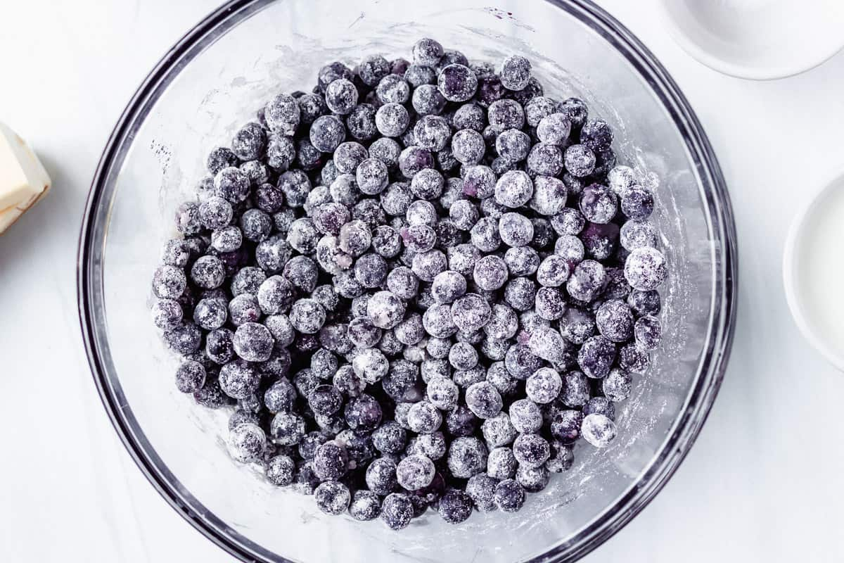 Sugared blueberries in a large glass bowl over a white background
