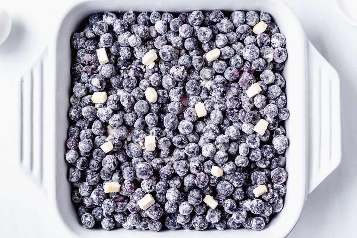 Sugared blueberries in a casserole dish with dots of butter all over the top