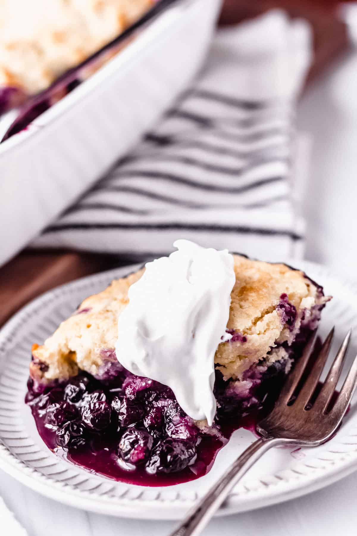 Close up of blueberry cobbler on a white plate with a fork and a striped towel in the background