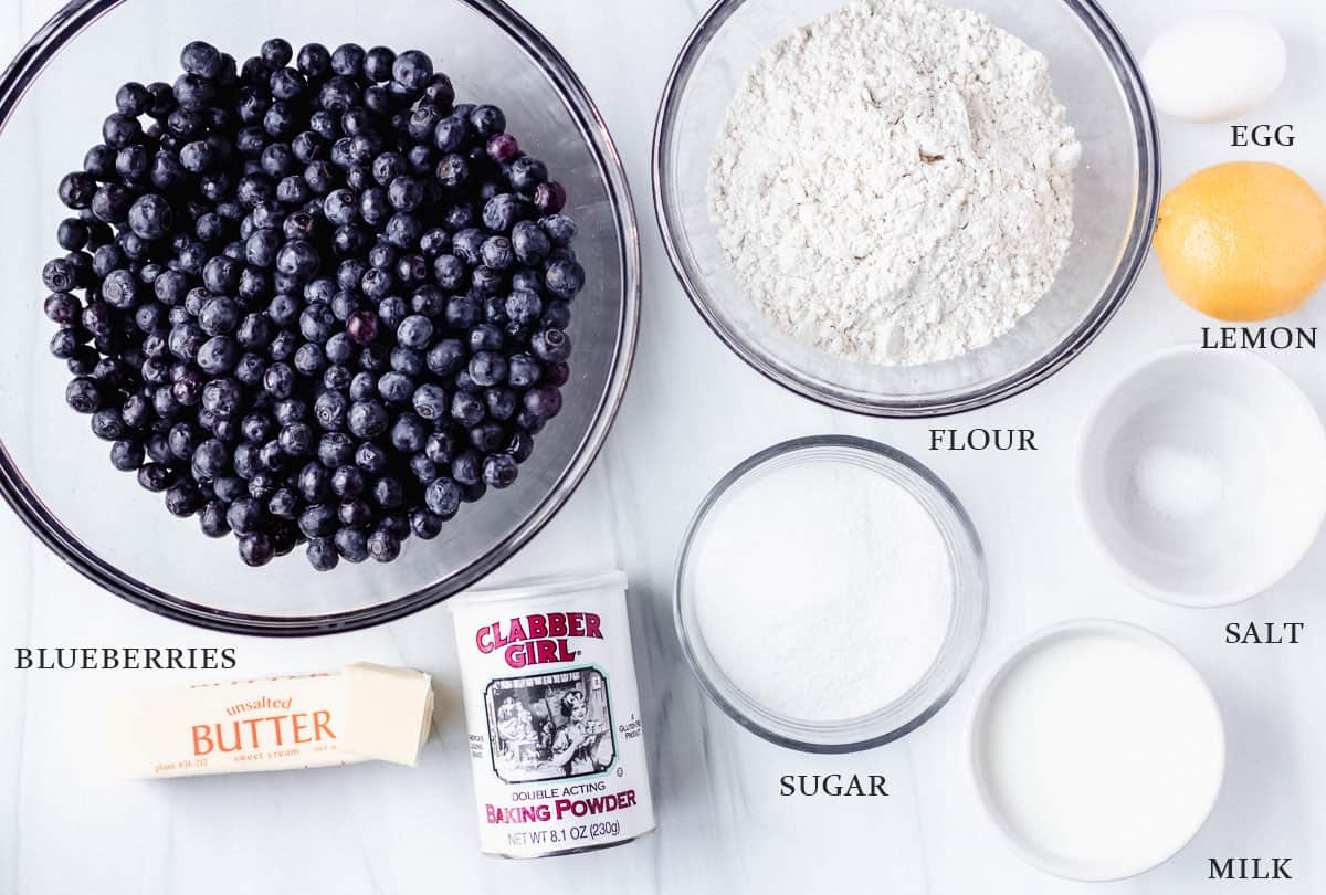 Ingredients to make blueberry cobbler on a white backdrop with labels