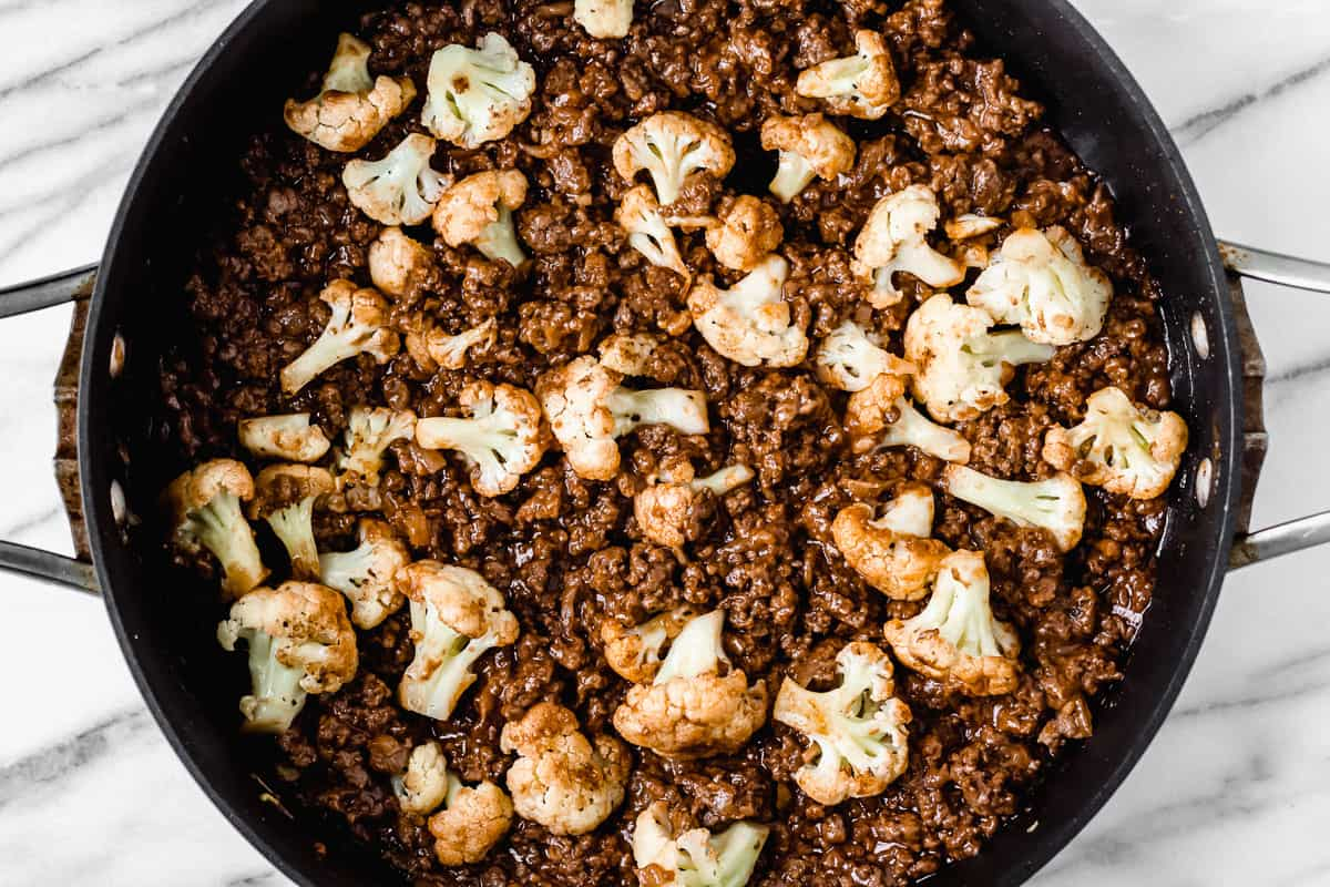 Barbecue ground beef and cauliflower florets in a black skillet