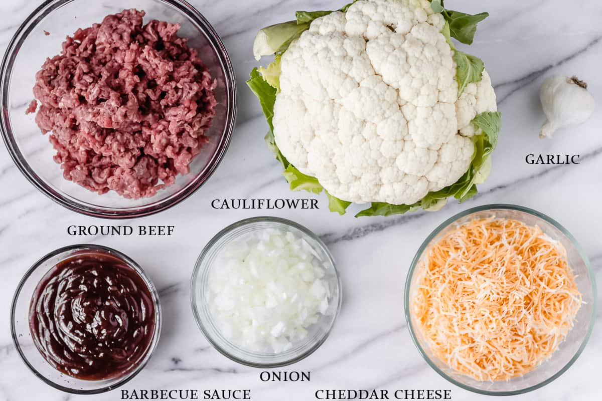 Ingredients for a barbecue ground beef and cauliflower skillet on a marble table with labels