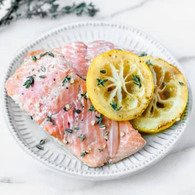 Poached salmon with lemon slices on a plate