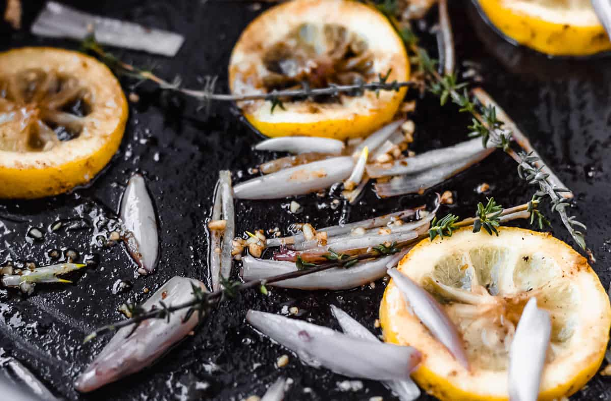 Lemons, shallots, garlic and butter close up in a black skillet