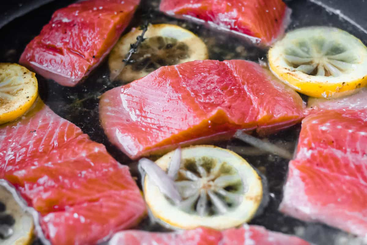 Salmon fillets with lemon slices and shallots in a black skillet