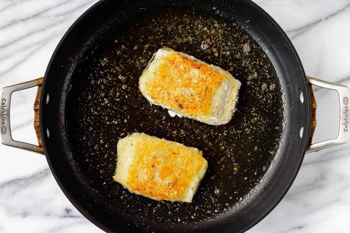 2 potato crusted cod fish fillets in a black skillet