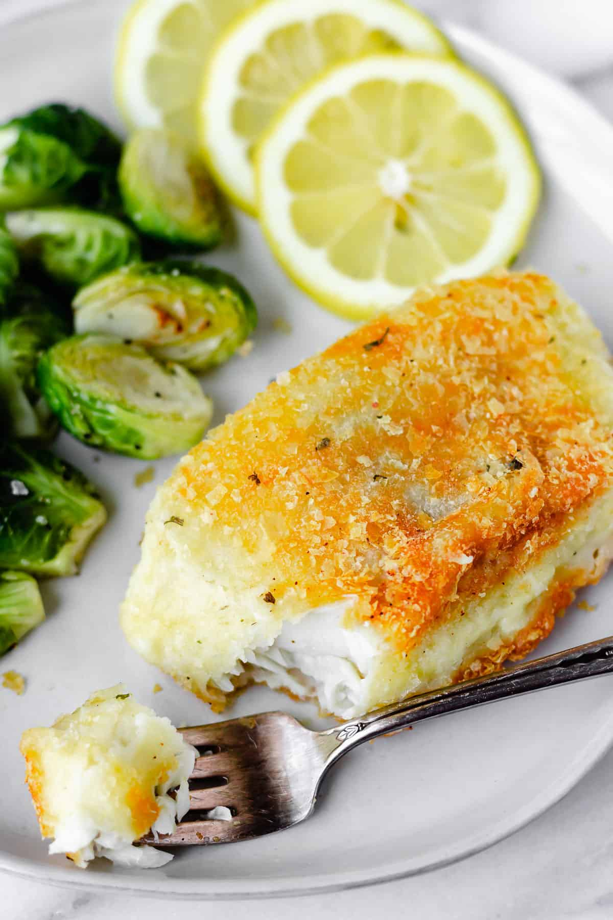 A bite of potato crusted cod on a fork in front of the rest of the fillet with brussels sprouts and lemon slices in the background