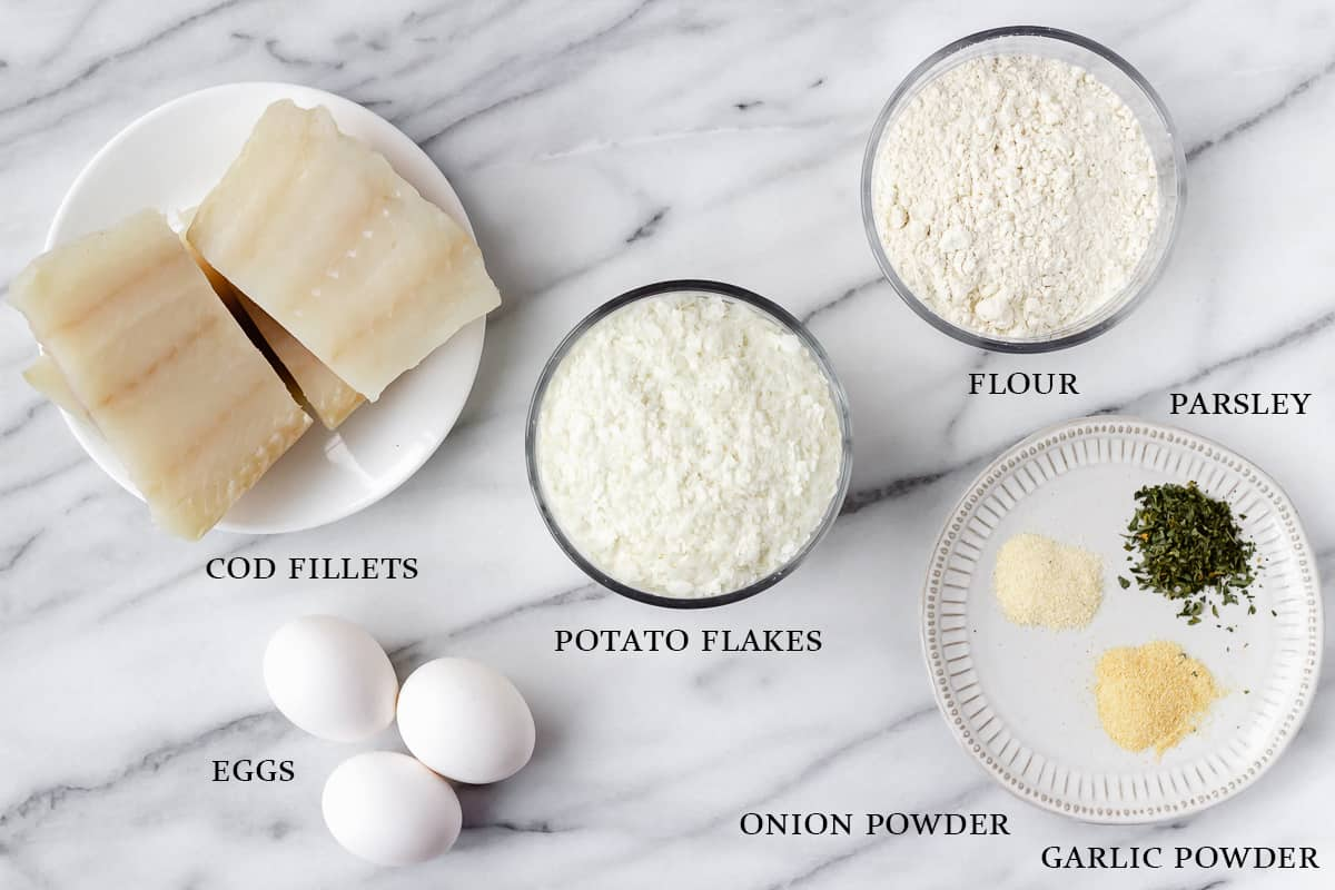 Ingredients needed to make potato crusted cod fish on a marble backdrop with labels