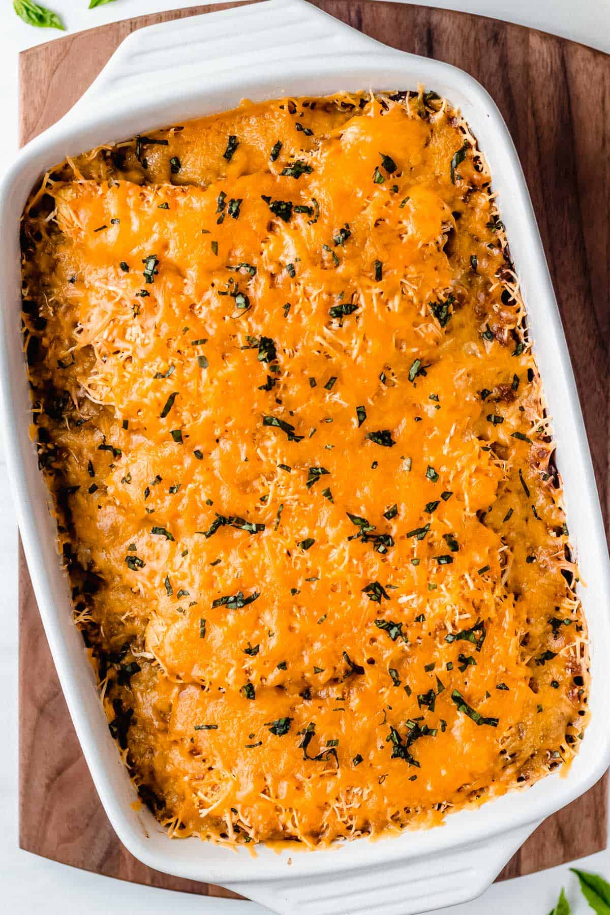 Baked sweet plantain lasagna in a rectangular casserole dish over a wood board