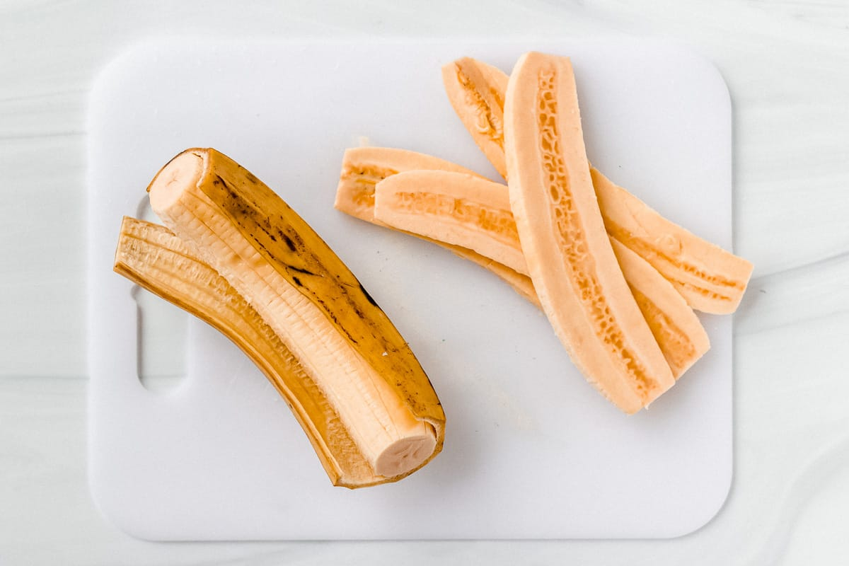A partially peel plantain and 4 plantain slices on a cutting board