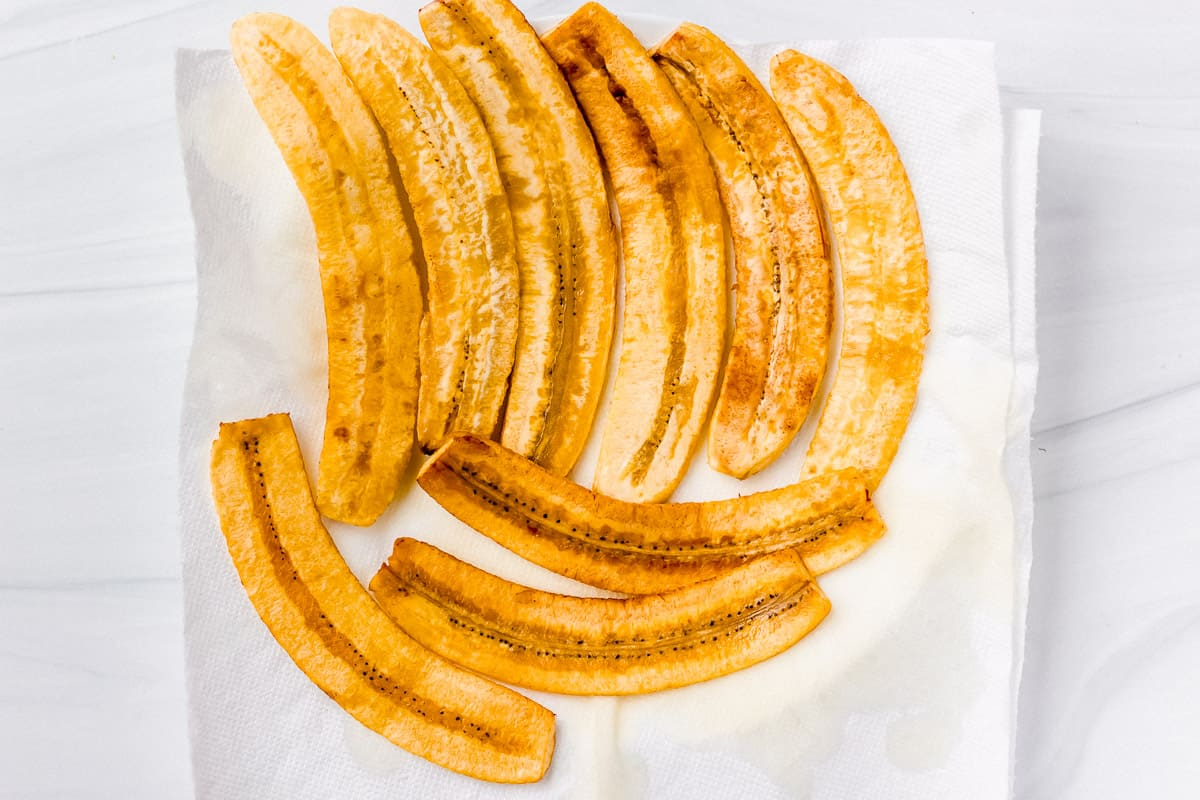 Fried plantain sliced on a paper towel lined plate