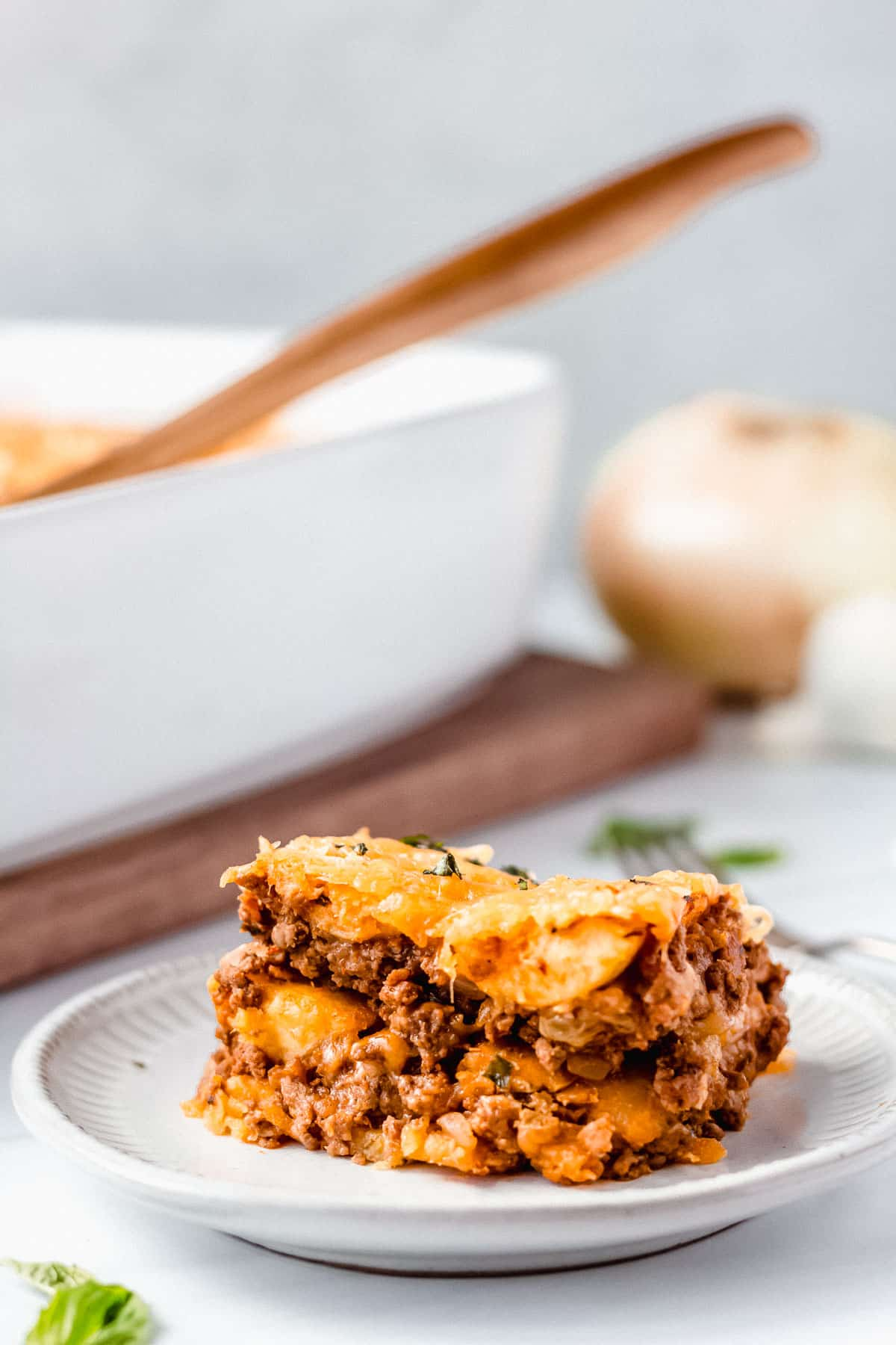 Close up of sweet plantain lasagna on a white plate with the casserole dish, server and onion in the background