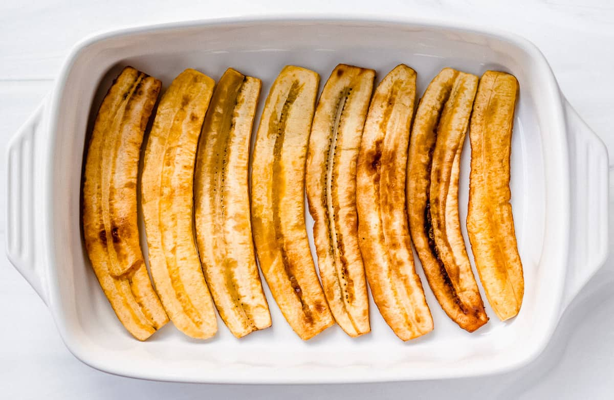 Plantain sliced in the bottom of a rectangular casserole dish