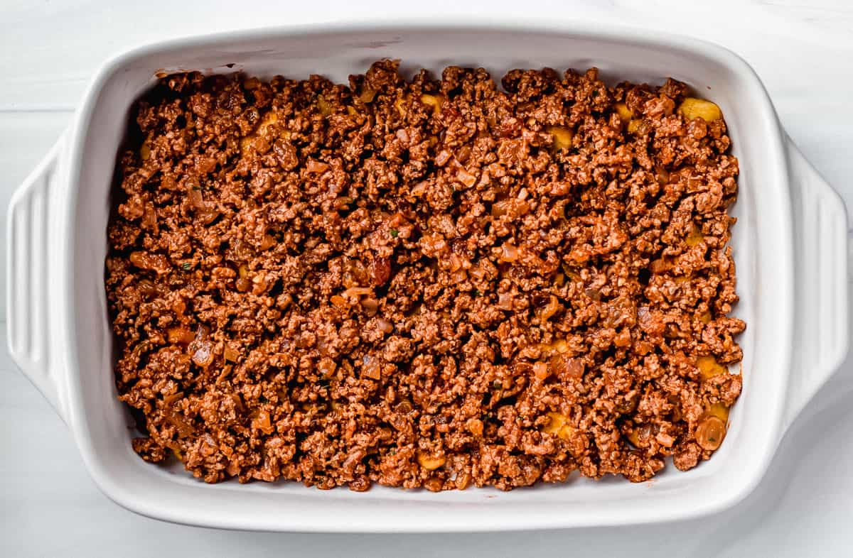 Ground beef on top of plantain slices in a rectangular casserole dish