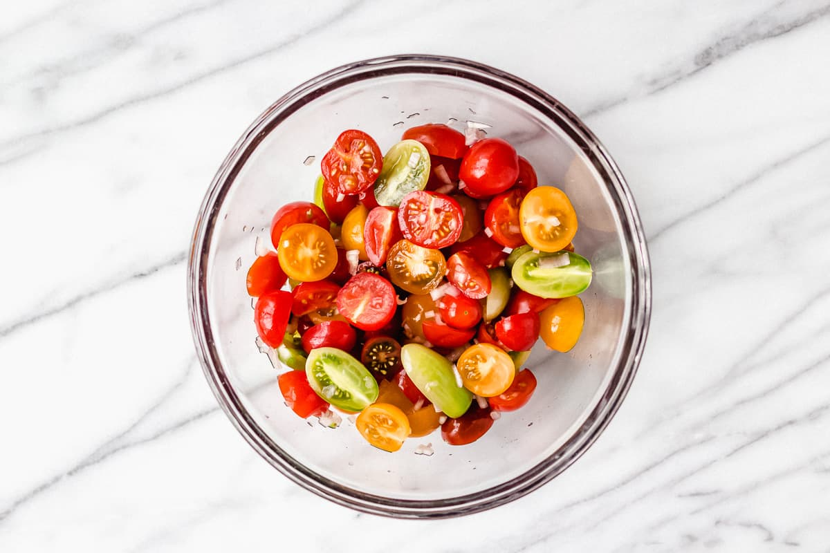 Different color tomatoes in a glass bowl and shallots on a marble background