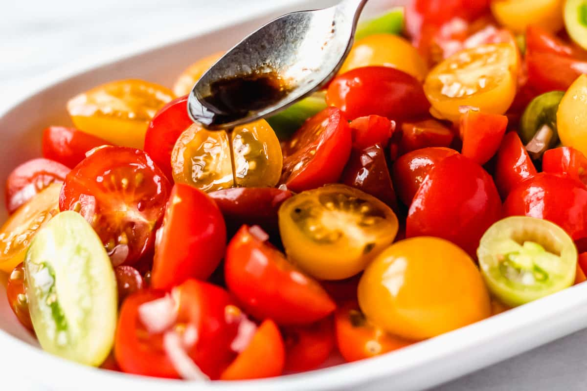 Balsamic dressing being drizzled over tomatoes