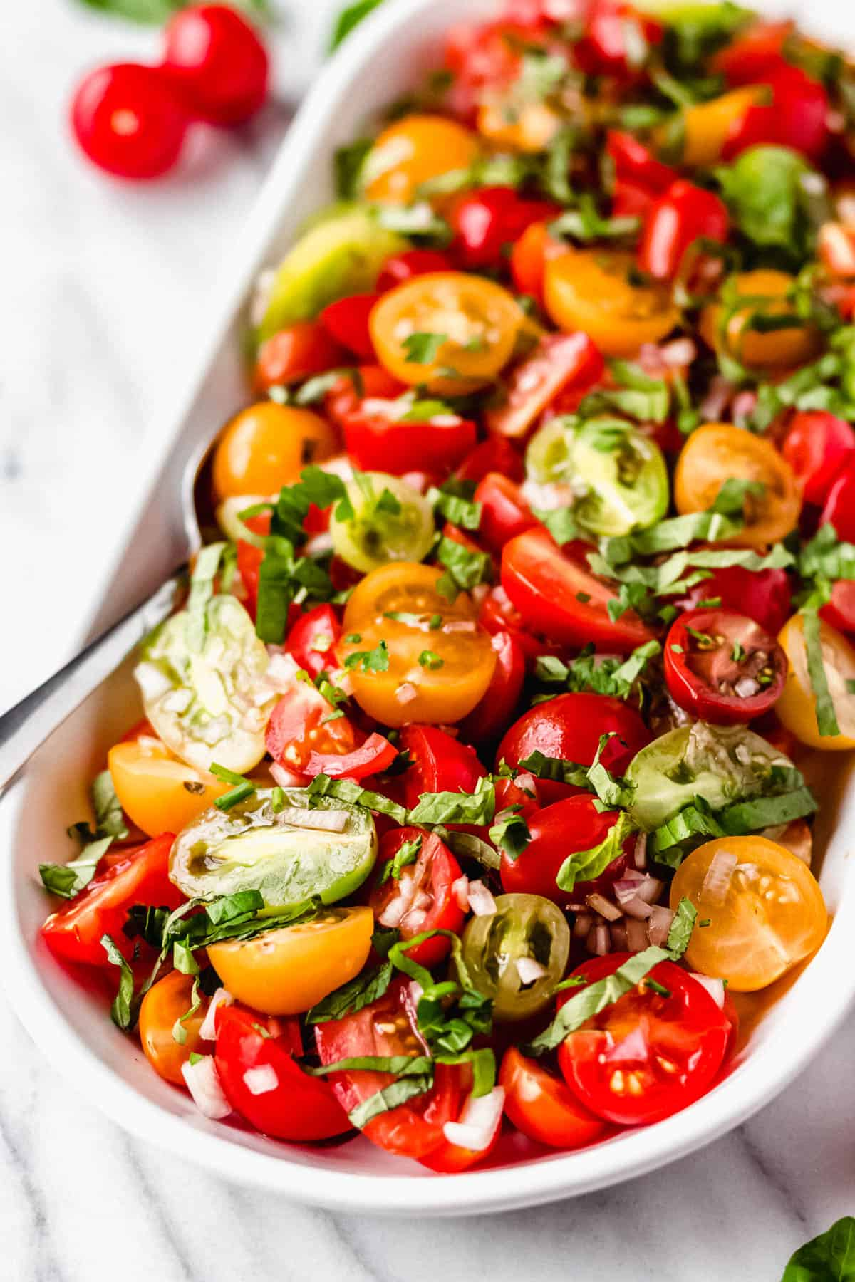 Close up of tomato basil salad with a serving spoon in it