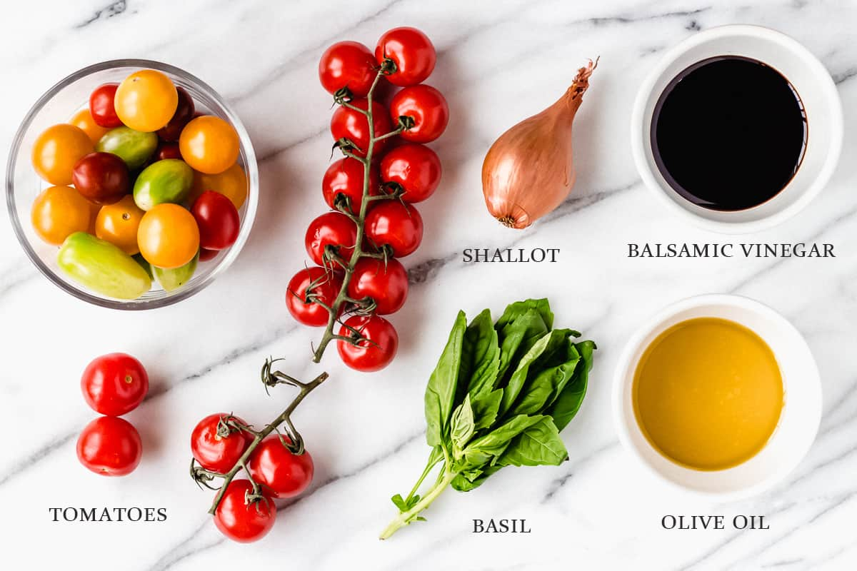 Ingredients to make tomato basil salad on a marble background with labels