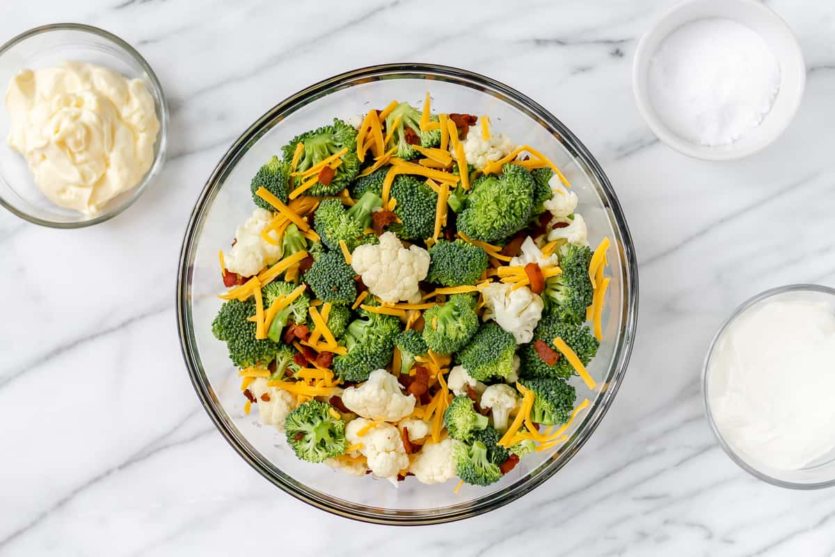 Broccoli, cauliflower, cheese, bacon and shallot mixed in a glass bowl with other bowls of ingredients around it