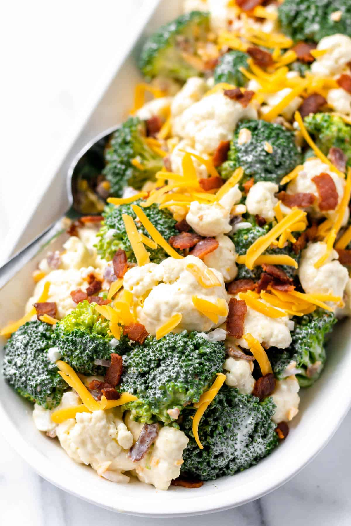Close up of amish broccoli salad in an oval serving dish with a spoon