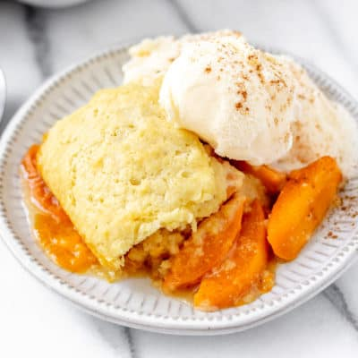 Close up of apricot cobbler and ice cream on a white plate