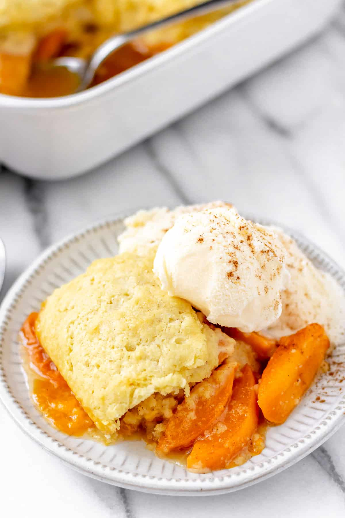 A serving of apricot cobbler with ice cream and the baking dish in the background