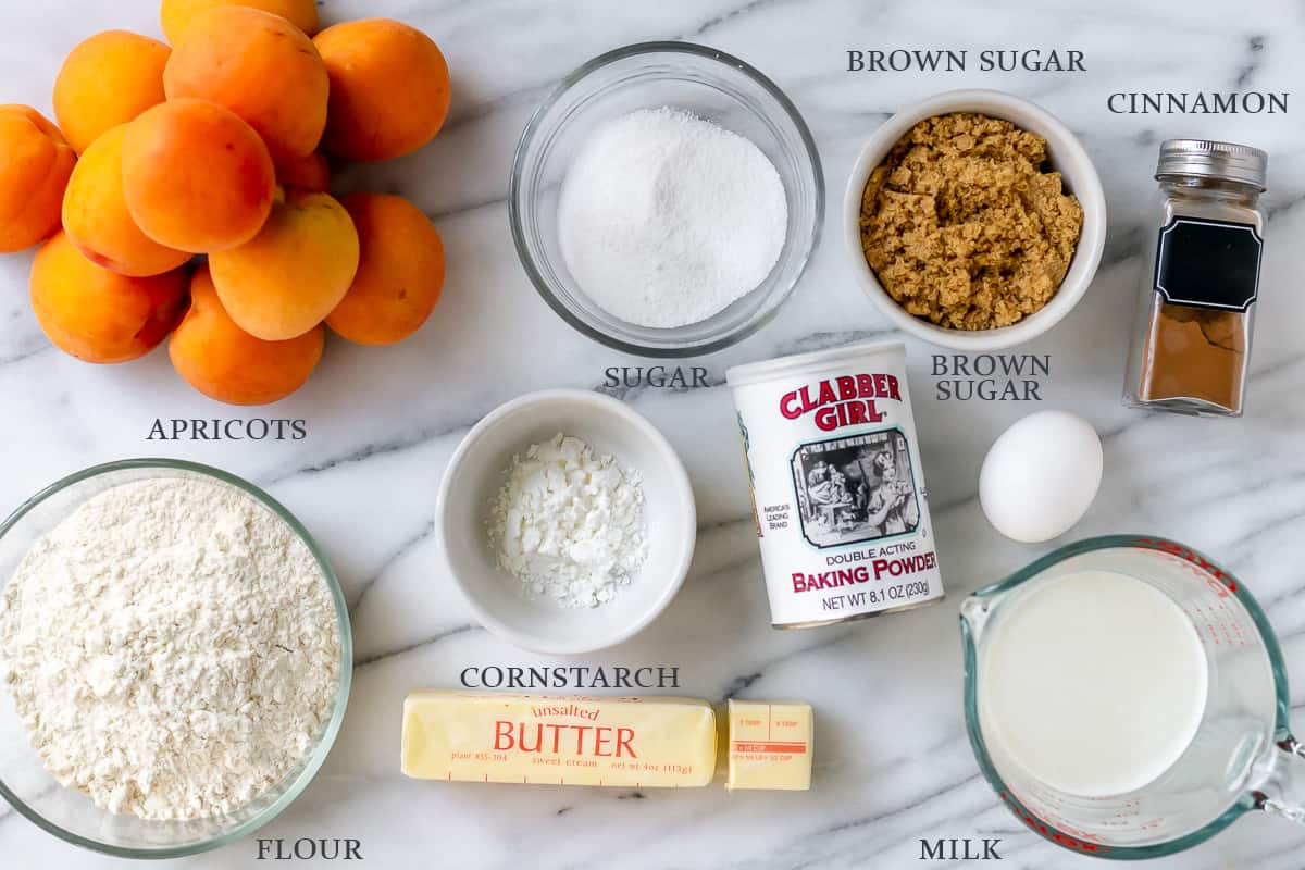 Ingredients needed to make apricot cobbler on a white background with labels