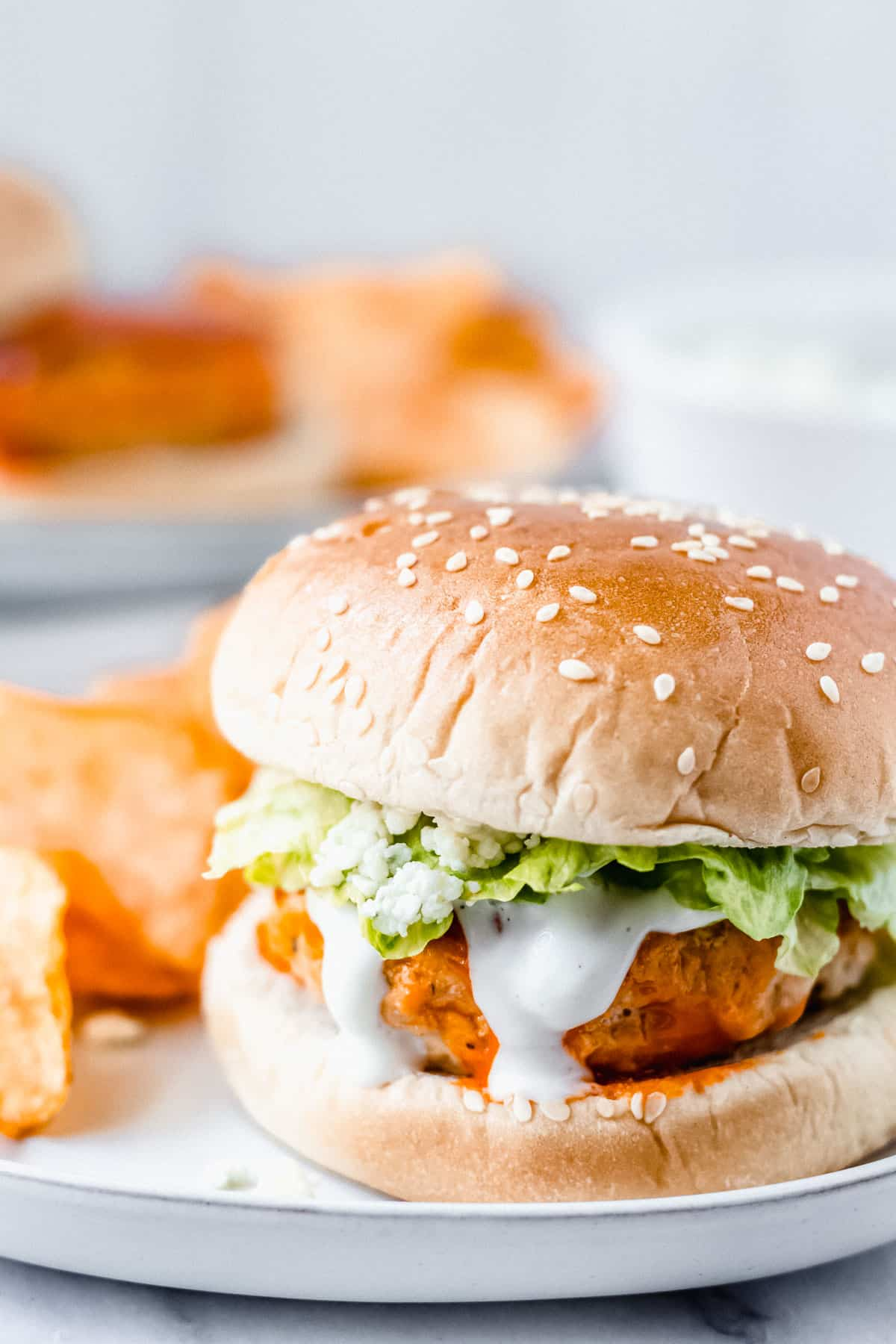 A buffalo chicken burger on a plate with potato chips and a second plate and small white bowl blurred in the background