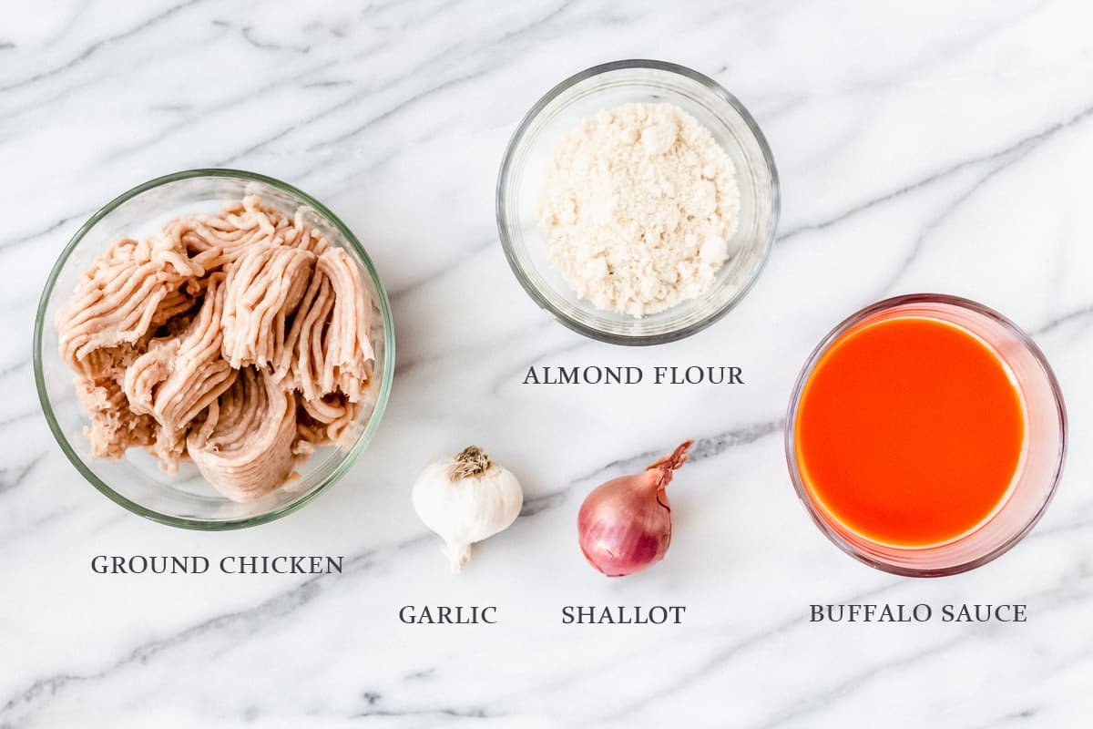 Ingredients to make buffalo chicken burgers on a marble backdrop with labels