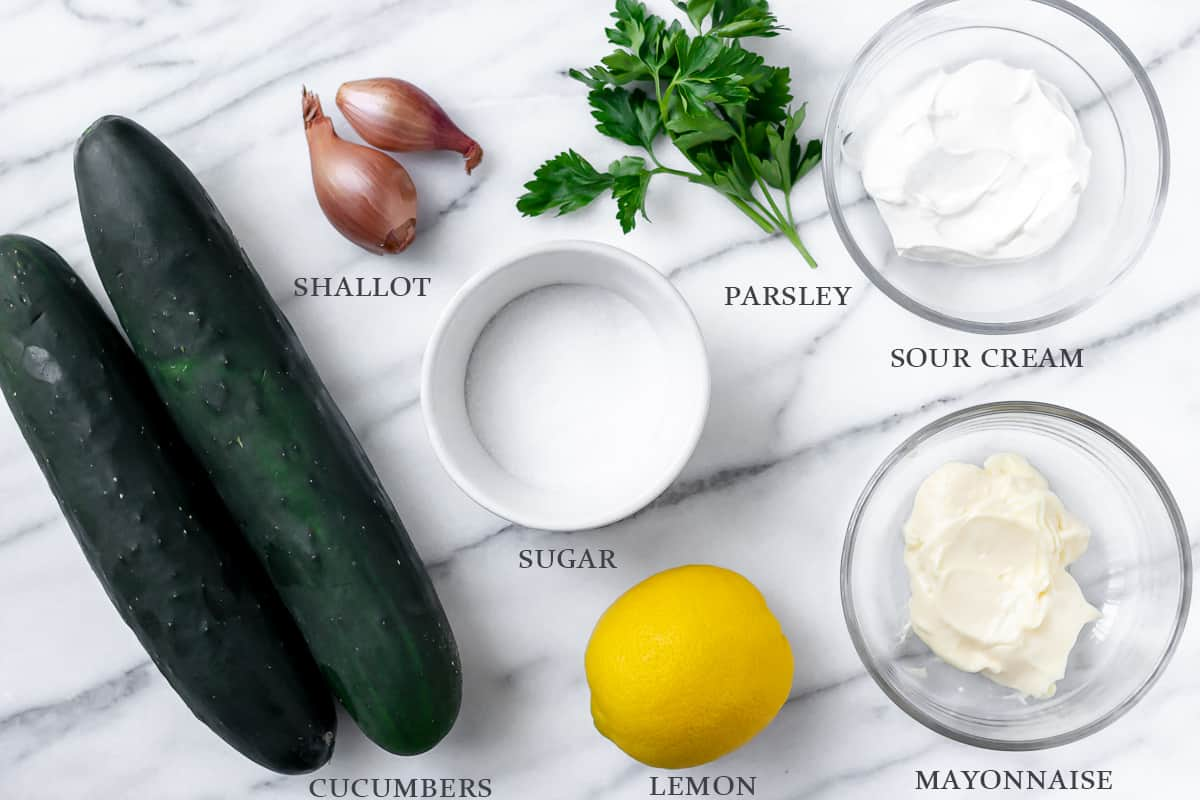 Ingredients needed to make creamy cucumber salad on a marble backdrop with labels