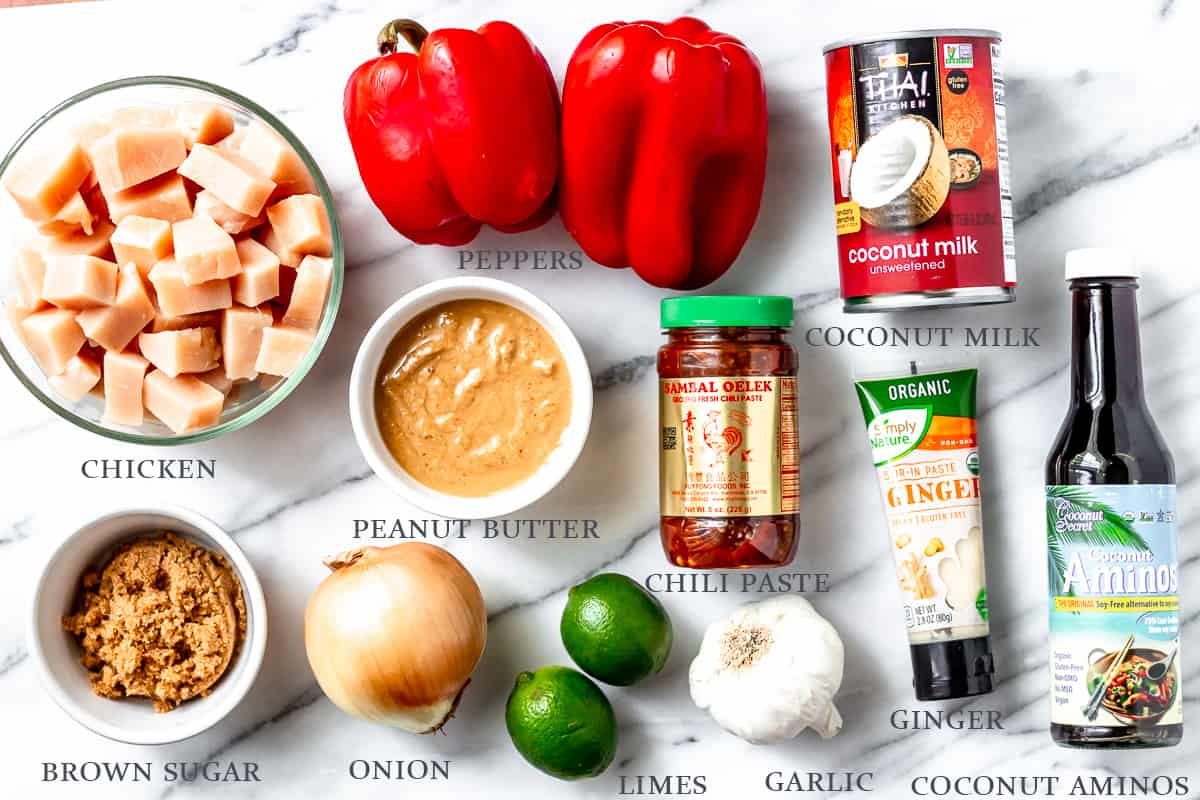 Ingredients needed to make peanut butter chicken on a marble background with labels