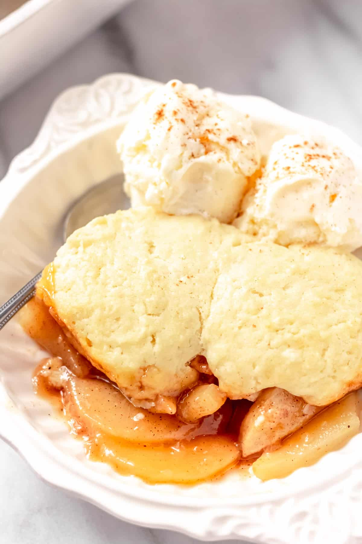 Close up of pear cobbler in a bowl with ice cream and a spoon