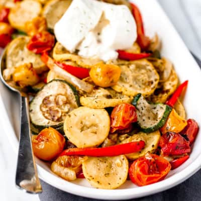 Close up of roasted summer vegetables on a white serving tray with a spoon