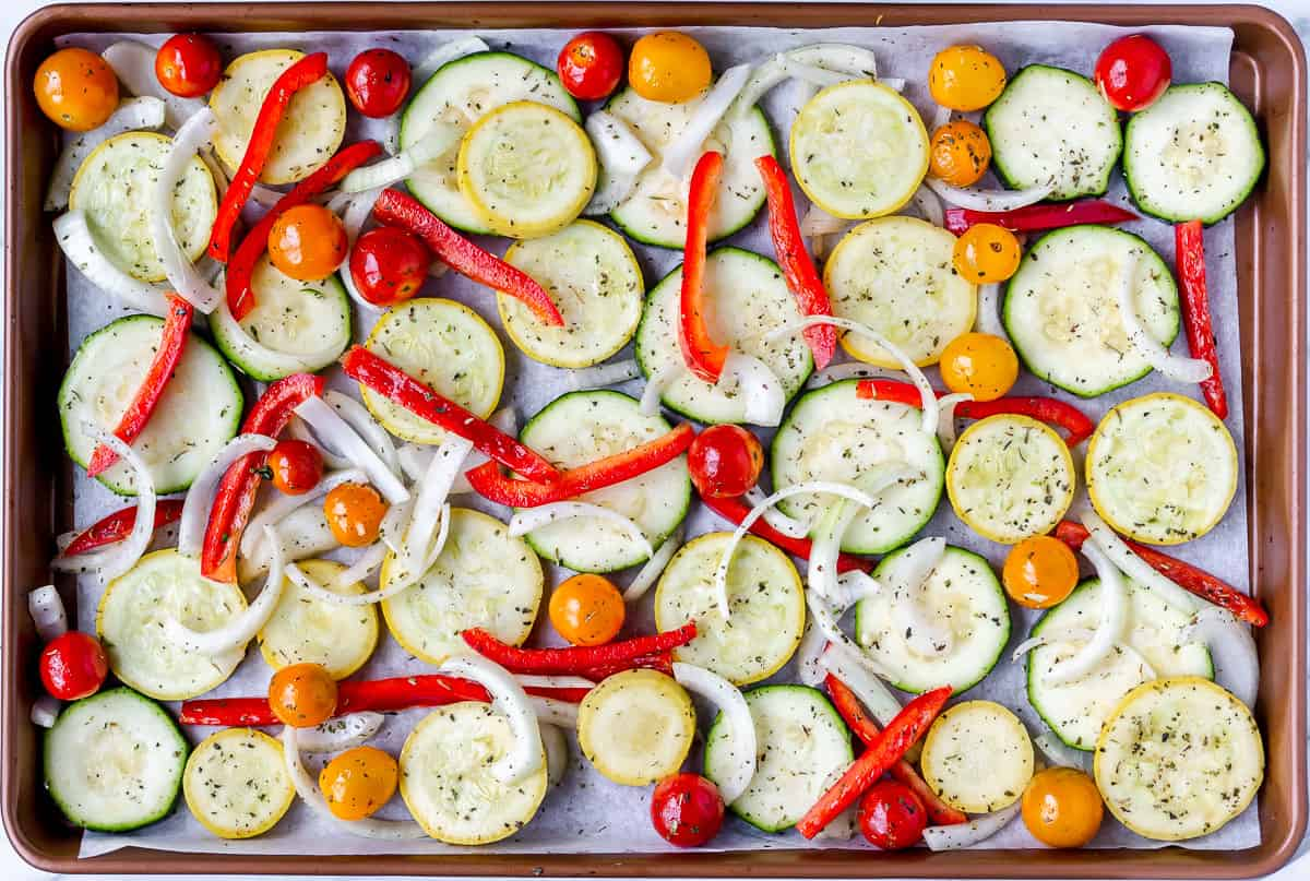 Summer vegetables spread out on a baking sheet