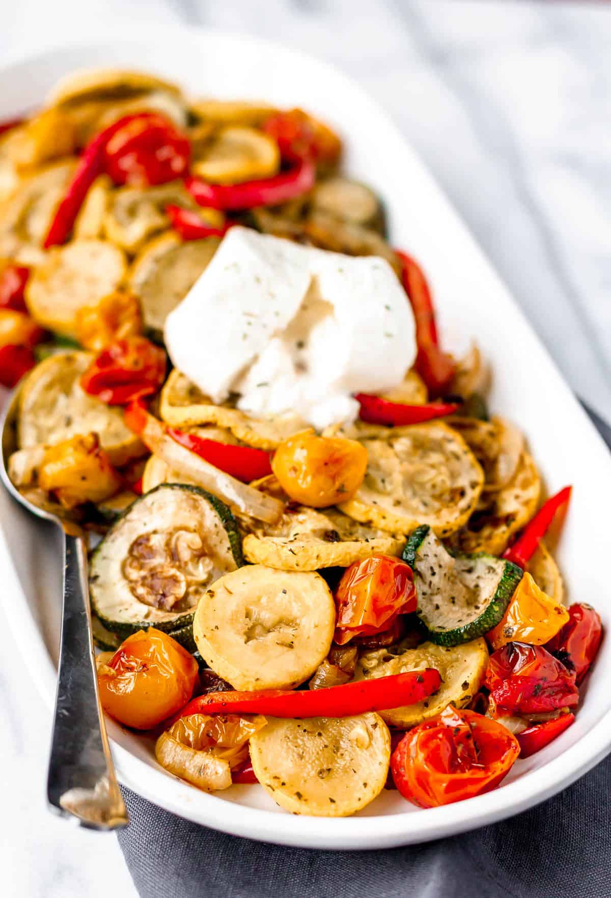 Roasted summer vegetables with burrata on a white serving dish with a spoon
