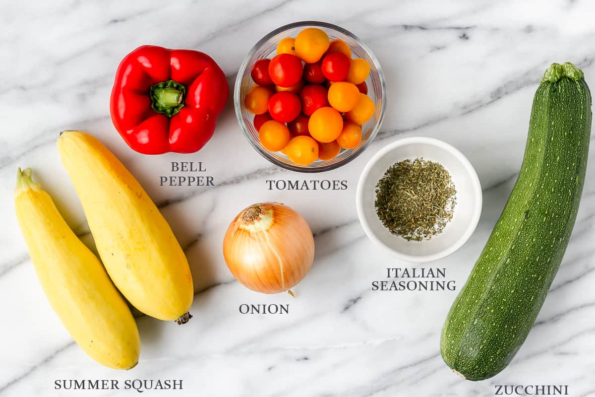 Ingredients to make summer roasted vegetables with labels on a marble backdrop