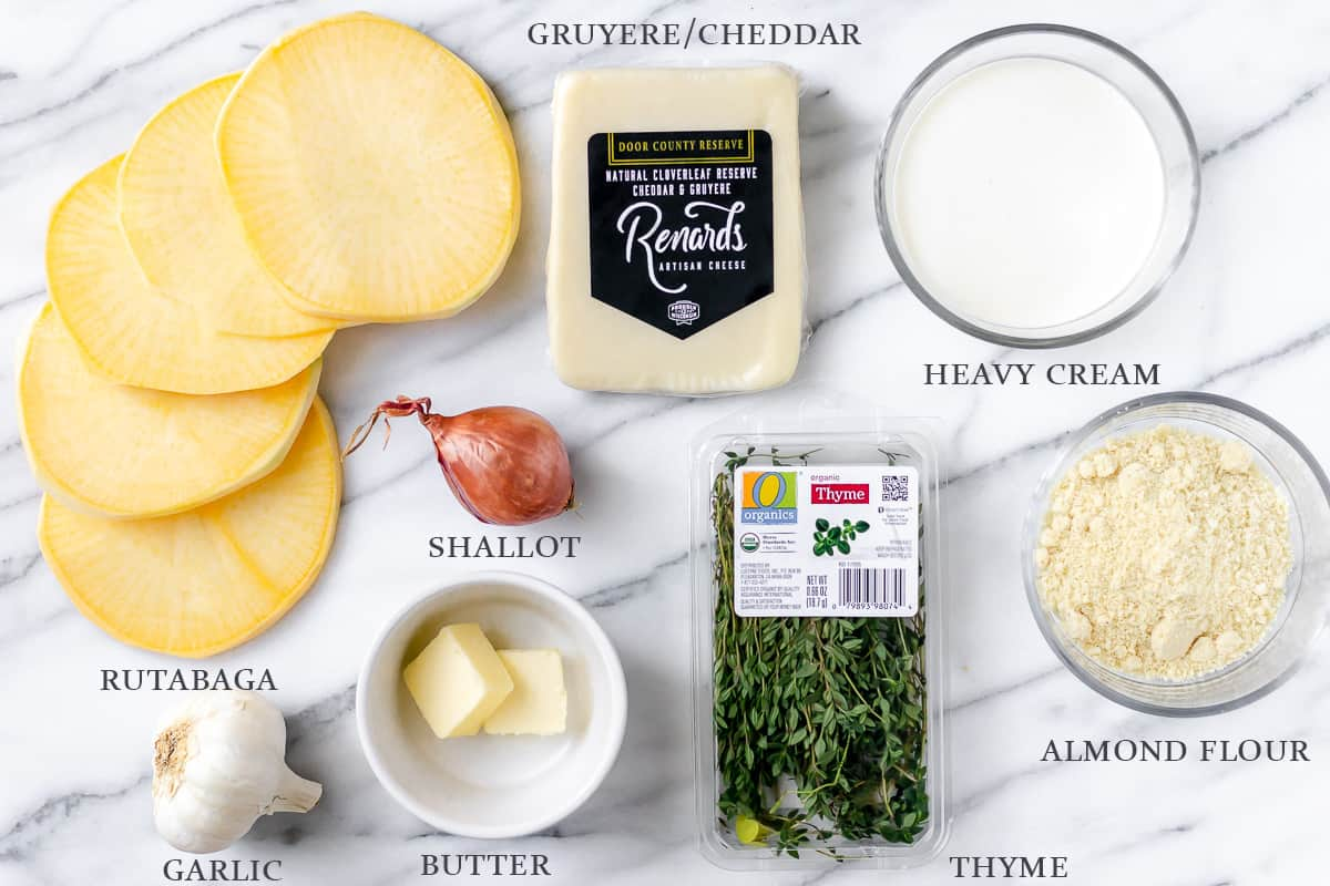 Ingredients needed to make rutabaga gratin on a marble backdrop with labels