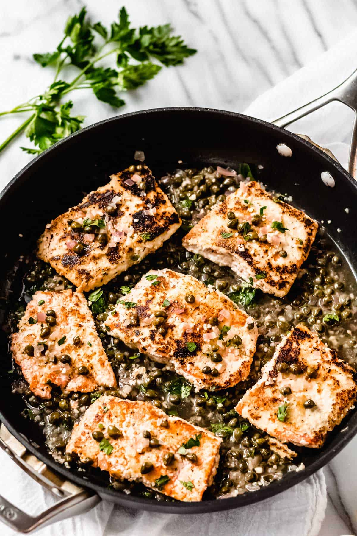 Salmon piccata in a black skillet with parsley in the background