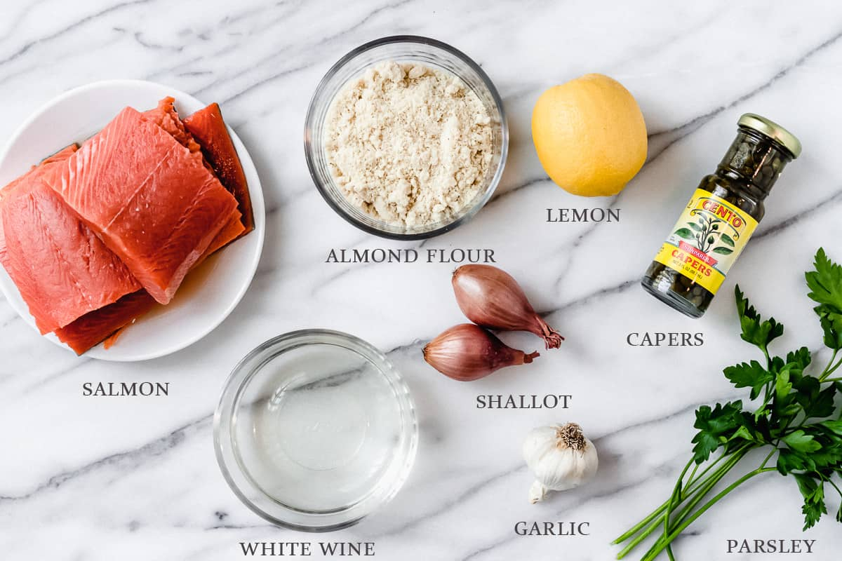 Ingredients needed to make salmon piccata on a marble. background with labels