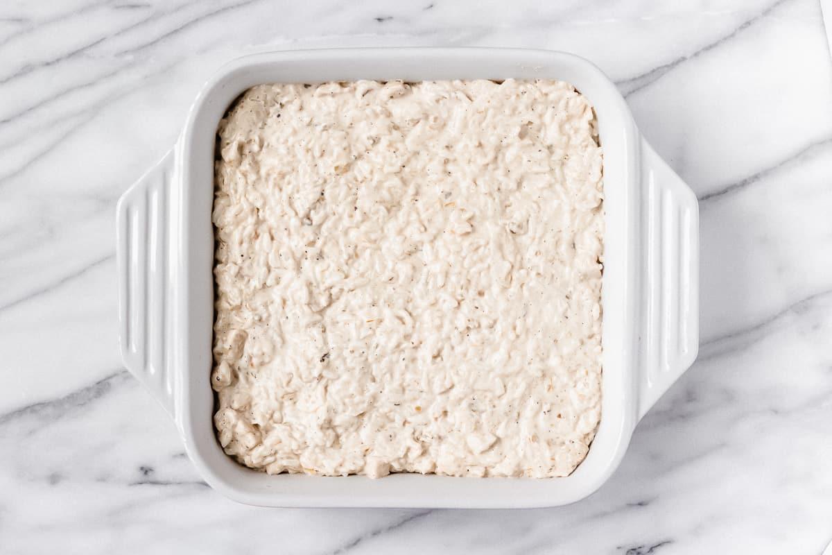 Creamy chicken and rice in a white square casserole dish