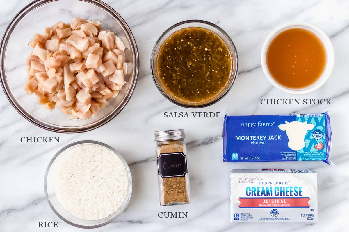 Ingredients needed to make salsa verde chicken casserole on a marble backdrop with labels