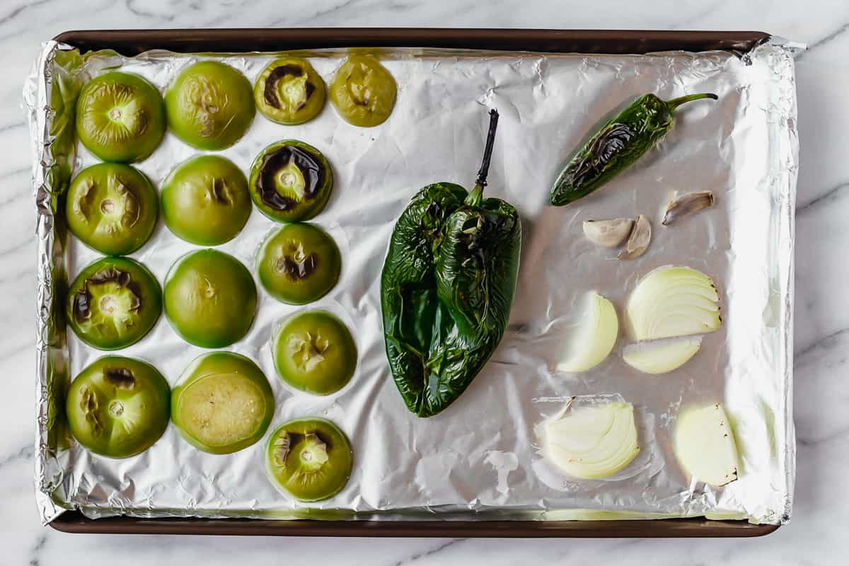 Roasted tomatillos, poblano, jalapeno, onion and garlic on a foil covered sheet pan
