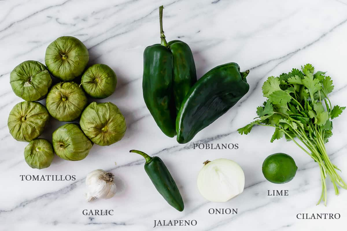 Ingredients needed to make tomatillo enchilada sauce on a marble backdrop with labels